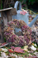 Autumn wreath made from dried hydrangea flowers, sedum plant, cones, and hay