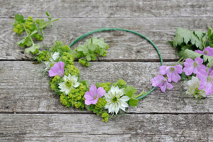 Tie a summer wreath of lady's mantle, cranesbill, and maiden in the countryside on a wire ring