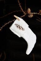 Handmade Christmas-stocking decoration hung on larch branch