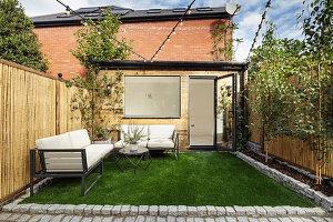 Kleiner Reihenhausgarten mit Rasenfläche und Outdoor-Sofas