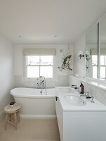 White bathroom with twin washstand and bathtub below lattice window