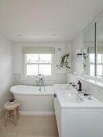 Badezimmer in Weiß mit Doppelwaschtisch und Badewanne unter Sprossenfenster
