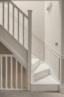 Treppenaufgang ganz in Weiß mit Holzgeländer und halbhoher Wandvertäfelung