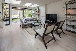 Sitzbereich am Fernseher in Wohnzimmer mit Oberlichtfenstern und Fensterfront zum Garten