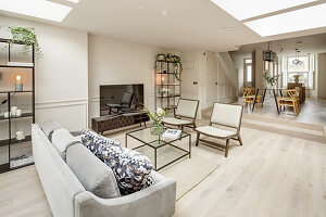 Seating area around TV and dining table on raised level in open-plan living room
