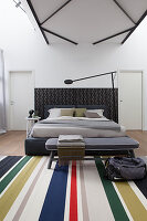 Double bed, bedroom bench and striped rug in loft apartment