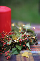 Autumn arrangement of sprigs of berries, fairy lights and candle
