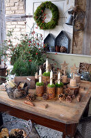 Rural Advent decoration with candles in tin cans and a flower arrangement made of branches