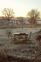 Table and chairs in wintry garden