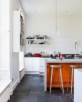 Island counter and orange accents in large, open-plan kitchen