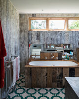 Bathtub with reclaimed-wood surround in rustic bathroom with board wall