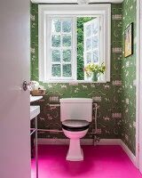 Toilet in small bathroom with hot-pink floor and green wallpaper