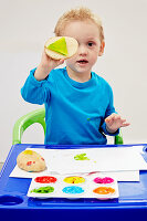 Little by making potato prints with colourful finger paint