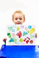 Kleiner Junge präsentiert stolz sein selbstgemachtes Stempeldruck-Bild