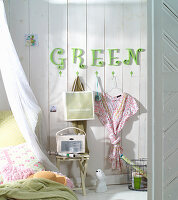 Green letters on wall above coat pegs in bedroom