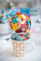 Ball decorated with brightly coloured buttons in mug of pompoms