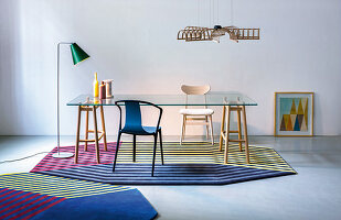 Glass table with wooden frame on octagonal striped rugs