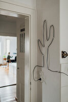 Electrical cable whimsically pinned to the wall in the shape of a cactus