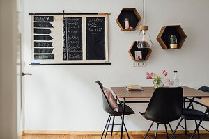 Chalkboard wall planner and hexagonal shelf modules above table