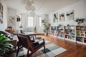 Retro armchairs in living room with half-height shelving