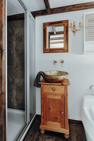 Gilt sink on wooden base cabinet in small bathroom