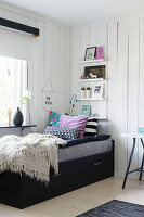 Black bed with drawers below in child's bedroom with board walls