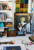 Antlers, paintings and knick-knacks between two sets of shelves