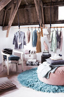 Clothes rail below wooden ceiling in rustic bedroom in pastel shades