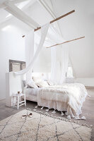 Bed with canopy in white attic bedroom