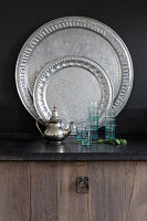 Silver teapot and glasses in front of Oriental trays