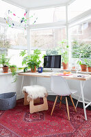 Desk, houseplants and red rug in window bay