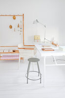 Metal stool and chair at desk on white wooden floor