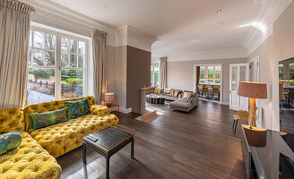Mustard-yellow, button-tufted chaise sofa in elegant, split-level living room