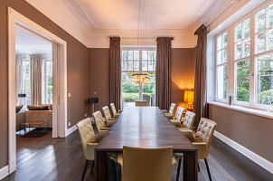 Elegant dining room in shades of brown with long wooden table and leather chairs