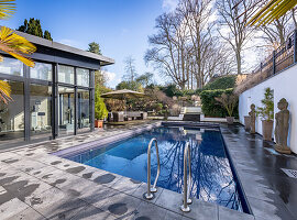 Swimming pool in garden area decorated with antique statues