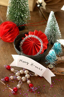 Christmas greeting on small banner, miniature Christmas trees and decorations