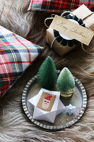Paper star and miniature trees on plate next to wrapped gift
