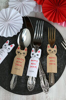 New Year's greetings and names on cat-shaped paper tags