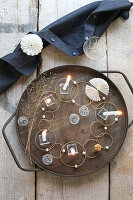 Original arrangement on table with glass, wire balls, beads, rings and candles on wooden tray
