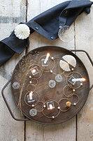Origineller Tischschmuck aus Glas, Drahtbällen, Perlen und Ringen mit Kerzen auf Holztablett