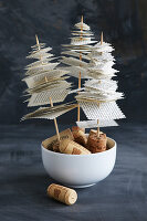 Miniature fir trees made from skewered book pages on cork bases against black background