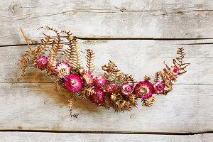 Kleine Girlande mit Strohblumen-Blüten auf getrocknetem Farnblatt