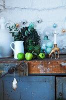 Krug mit Eukalyptuszweig, grüne Äpfel, Glasbehälter und Kerzenhalter auf altem Schrank