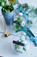 Glass baubles filled with leaves and labelled with Christmas greetings