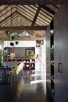 Rustikales Esszimmer mit offener Balkendecke und grauem Boden