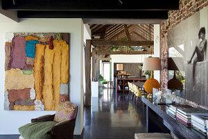 Blick vom Wohnzimmer mit Gemälden ins rustikale Esszimmer