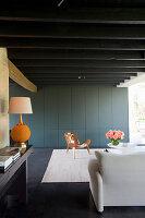 Blaugraue Schrankwand im Wohnzimmer mit schwarzer Balkendecke