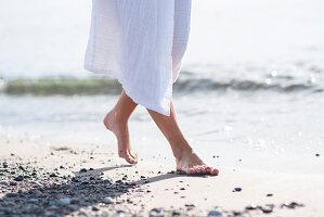 Frau in weißem Bademantel am Strand