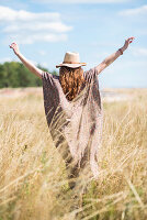 Woman with long hair wearing summer hat standing in field