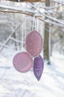 DIY-Baumanhänger aus Filz mit Stickerei an Ast im verschneiten Garten
